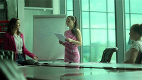 The presentation of businesswoman in business center. Three businesswomen working in office building. Young woman presents some information near the white board stock video footage