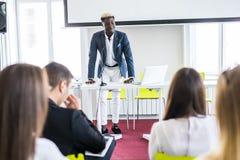 presentation för Afro--amerikan affärsmandanande av ett affärsplan på flipcharten affären chairs konferensskrivbordet som isolera fotografering för bildbyråer
