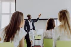 presentation för Afro--amerikan affärsmandanande av ett affärsplan på flipcharten affären chairs konferensskrivbordet som isolera royaltyfria foton