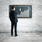 Presentation and finance concept. Handsome european businessman drawing business chart on chalkboard in interior. Presentation and finance concept. 3D Rendering Stock Photography