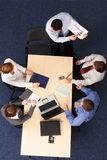 Presentation, five people. A group of business people listening to a presentation.Aerial shot taken from directly above the table stock photos