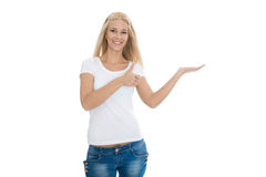 Presentation gesture: Isolated young blond woman presenting with Stock Image