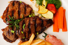 Presentation of grilled steak chips vegetables Stock Photo