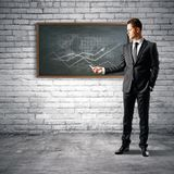 Presentation and income concept. Handsome european businessman drawing business chart on chalkboard in interior. Presentation and income concept. 3D Rendering Stock Photo