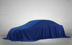 Presentation of New Car With Question Mark wrapped under a sheet Gift red bow, Close up a new car hidden under cover. Stock Photo
