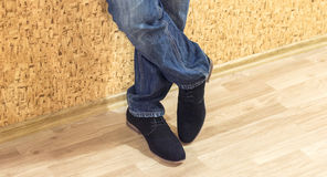 Presentation of new models of men's suede shoes and jeans. Against a wall with wallpaper Royalty Free Stock Photography
