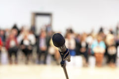 Presentation. Public speaking. Microphone in focus against blurred audience stock photo
