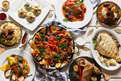 Presentation of variety georgian cuisine. In restaurant. Stewed mutton and vegetables, grilled fish, khinkali, shawarma and other meat dishes with souce stock images