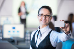 Presentation. Young smiling business woman is holding a discount card while sitting in modern conference hall during presentation Stock Images
