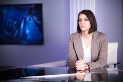 Presentatore di televisione castana bello giovane allo studio durante la radiodiffusione in tensione Direttore femminile della TV fotografie stock