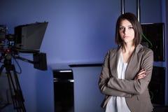 Presentatore di televisione castana bello giovane allo studio durante la radiodiffusione in tensione Direttore femminile della TV Immagine Stock