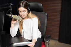 Presentatore radiofonico femminile che trasmette per radio una manifestazione immagine stock