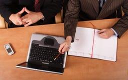 Presentazione - 2 uomini che lavorano allo scrittorio nell'ufficio fotografia stock libera da diritti