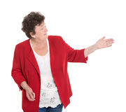 Presentazione senior femminile soddisfatta sopra il bianco con la sua mano Immagine Stock Libera da Diritti