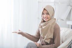 Presentazione sorridente della giovane donna attraente allo spazio della copia Immagine Stock