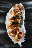 Presentazione sulla Bruschetta di legno della tavola con i fichi ed il prosciutto di Parma Concetto dei pani tostati sani della p fotografia stock