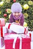 Presente aberto do Natal do menino Excited sob a árvore na neve Imagens de Stock