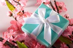 Presente com as folhas cor-de-rosa da flor e do verde fotografia de stock royalty free
