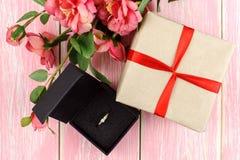 Presente com fita vermelha, anel na caixa e flores cor-de-rosa Imagem de Stock
