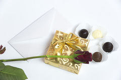 Presente con la letra, la rosa del rojo y el chocolate imágenes de archivo libres de regalías