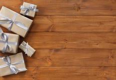Presente in contenitori di regalo sul fondo di legno della struttura Fotografie Stock