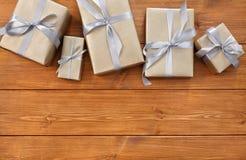 Presente in contenitori di regalo sul fondo di legno della struttura Immagini Stock