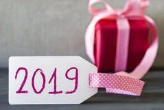 Presente cor-de-rosa, etiqueta, texto 2019, Gray Cement Background fotos de stock