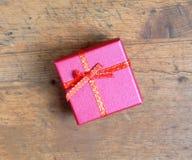 Presente de época natalícia pequeno na caixa de cor vermelha quadrada, coberta com a fita com curva na opinião superior do fundo  imagem de stock royalty free