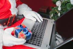 Presente de compra de Santa pelo pagamento em linha com os Internet banking imagem de stock