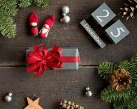Presente de Natal com fita, o calendário do Natal, ramos do pinho, o cone e as decorações vermelhos do xmas Fotografia de Stock