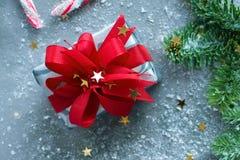 Presente de Natal com fita vermelha, as estrelas douradas, o abeto e os doces nos flocos de neve no fundo cinzento Foto de Stock Royalty Free