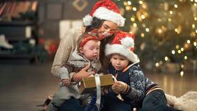 Presente de Natal da abertura da família na frente da árvore video estoque