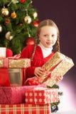 Presente de Natal da terra arrendada da menina na frente da árvore Imagens de Stock Royalty Free