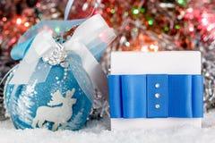 Presente de Natal e bola do Natal na neve contra um fundo do ouropel brilhante Fotografia de Stock Royalty Free