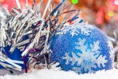 Presente de Natal e bola do Natal na neve contra um fundo do ouropel brilhante Luzes de incandescência Fotografia de Stock Royalty Free