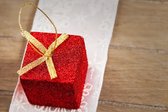 Presente de Natal minúsculo vermelho do brilho na madeira Imagem de Stock Royalty Free
