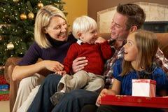 Presente di apertura della famiglia davanti all'albero di Natale Fotografie Stock