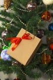 Presente do ano novo na árvore de Natal Fotografia de Stock Royalty Free