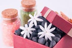 Presente do bem-estar em uma caixa vermelha com as pedras do zen e sais de banho pretos Imagens de Stock Royalty Free