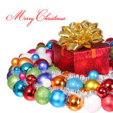 Presente do Natal com a curva do ouro e as bolas coloridas isoladas no whit Fotografia de Stock Royalty Free