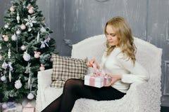 Presente do Natal da abertura da jovem mulher Foto de Stock