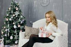 Presente do Natal da abertura da jovem mulher Imagens de Stock Royalty Free
