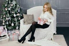 Presente do Natal da abertura da jovem mulher Foto de Stock Royalty Free