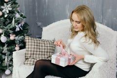 Presente do Natal da abertura da jovem mulher Fotos de Stock Royalty Free