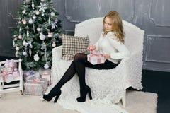 Presente do Natal da abertura da jovem mulher Imagens de Stock