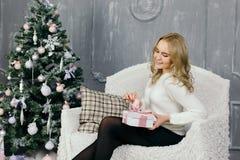 Presente do Natal da abertura da jovem mulher Imagem de Stock
