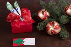 Presente do Natal do dinheiro com as bolas coloridas do Natal no fundo de madeira rústico Imagens de Stock