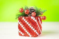 Presente do Natal na caixa vermelha em um fundo verde e branco a tabela A decoração do abeto ramifica grânulos Fotos de Stock