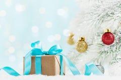 Presente do Natal ou árvore atual da caixa e de abeto com as decorações das bolas contra o fundo do bokeh de turquesa Cartão do f imagem de stock