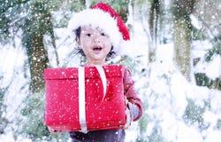 Presente do Natal pela menina de Santa na neve do inverno Foto de Stock Royalty Free